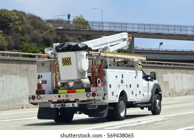 Rear and side view of utility truck with boom cherry picker on highway.