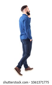 Rear side view of young elegant smart casual business man talking on the phone walking and looking up. Full body isolated on white background.