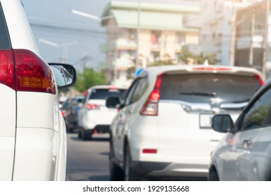Rear side of white car driving on the road in the city. During daytime and peak hours on work days.