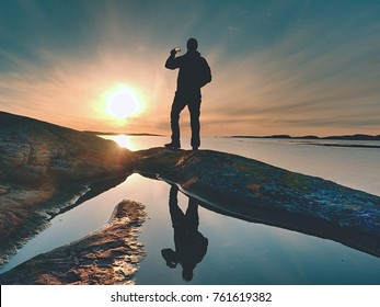 Rear silhouette of travelling man taking selfie at sea. Tourist with backpack standing on a rock, looking  over blue sea and taking photo by his smart phone camera