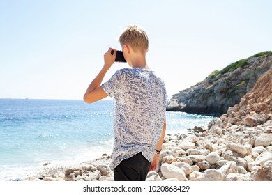 Rear of teenager young man using old photographic camera taking photos on beach landscape, practicing photo creative hobby, sunny outdoors. Male holding camera, travel leisure recreation lifestyle.