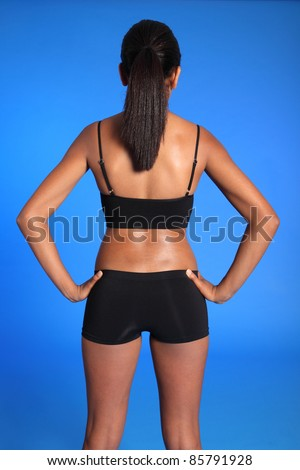 9b2a2fbf2008 Rear torso view of a beautiful healthy young african american woman wearing  black sports underwear, standing against blue background showing off fit  body.