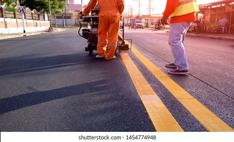 Rear view of 2 road workers with thermoplastic spray marking machine working to paint yellow lines on asphalt road surface with flare light in evening time, selective focus