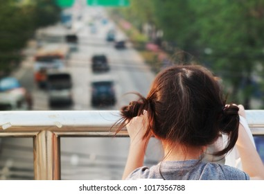 The rear view of 5 year old girl stand on the pedestrian overpass carrying plastic bag looking at the traffic down below.Girl  may in trouble or get lost.Concept of lonely child or kid violence.