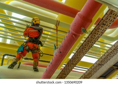 Rear view of abseiler wearing Personal Protective Equipment (PPE) such as body harness, orange coverall and yellow hard hat standing on gas pipeline managing his rope access for painting activities.