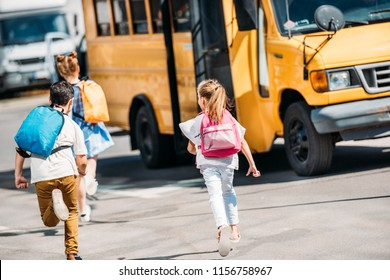 rear view of adorable schoolchildren running to school bus