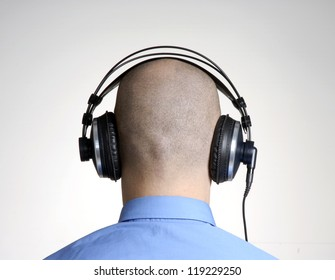 Rear view from an adult bald head man using headphones.