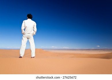 Rear view of an adult caucasian man standing on a sand dune over a clear blue sky. Erg Chebbi, Maroc