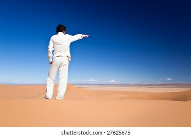 Rear view of an adult caucasian man standing on a sand dune pointing to somewhere. Erg Chebbi, Maroc