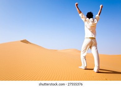 Rear view of a adult white man standing on a sand dune and holding arms up. Erg Chebbi, Maroc
