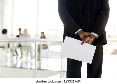 Rear view at african american businessman in suit standing holding papers behind back preparing for performance speech feel nervous afraid stressed before job interview, public speaking fear concept