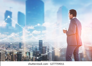 Rear view of African American businessman with coffee looking at graph in city sky. Toned image double exposure