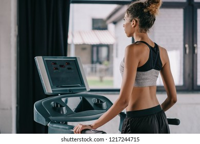 rear view of african american female athlete on treadmill at gym