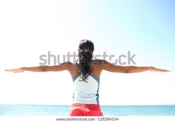 """Rear view of an """"african american"""" woman stretching her arms to the sides while standing against a deep blue sky, exercising on a sunny day by the sea."""
