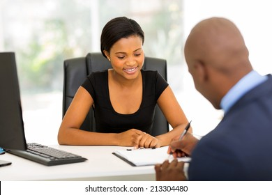 rear view of african businessman signing contract in office