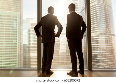 Rear view of african and caucasian businessmen wearing suits standing at full length large window enjoying great big city scenery, contemplative thoughtful multi ethnic partners building future plans