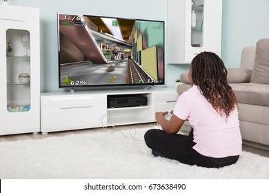 Rear View Of An African Girl Playing Video Games At Home