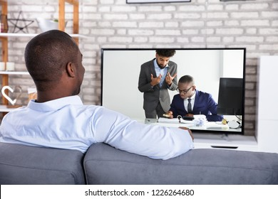 Rear View Of An African Man Watching Television At Home