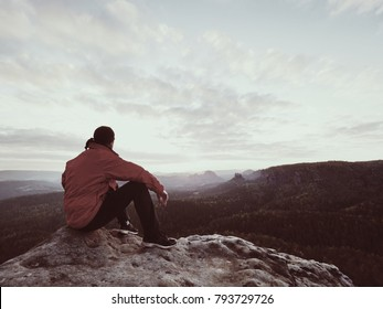 Rear view of alone hiker in dark red outdoor clothes sitting on rock. Sharp rocky peak  above mountains valley, cold Sun hidden in rainy clouds.