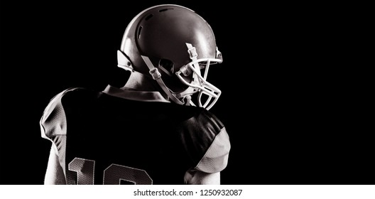 Rear view of American football player standing with rugby helmet