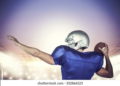 Rear view of American football player throwing ball against rugby stadium