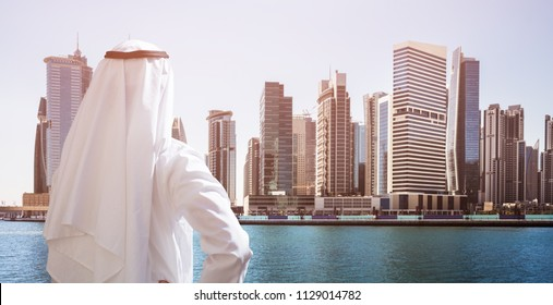 Rear View Of A Arabic Man Standing In Front Of Dubai Business Bay