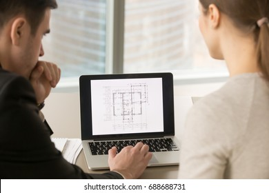Rear view at architects looking at pc screen while working with scanned copy of building plan, property value estimation, real estate appraisal, construction investment, close up, focus on laptop