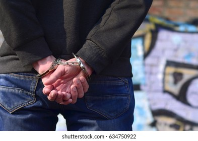 Rear view of the arrested and handcuffed offender against the graffiti background. The concept of preventing property damage, vandalism and combating hooliganism. anti-bullying concept