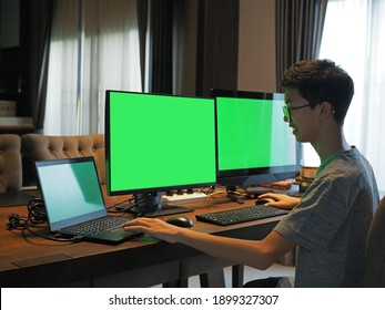 Rear view of an Asian boy working on three computer screens at home.