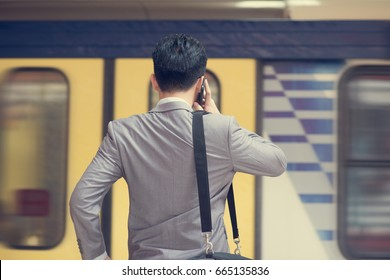 Rear view Asian business people using smart phone in subway station, train passing by at the background.