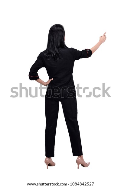 Rear view of asian business woman points finger at something posing isolated over white background