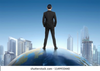Rear view of asian businessman standing on earth and looking at cityscape view with blue sky background