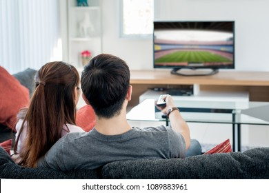 Rear view of Asian couple watching football at television in living room. Football festival concept.