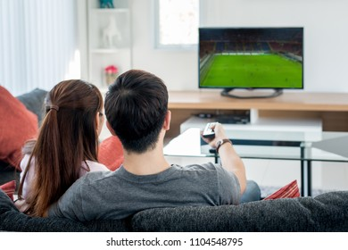 Rear view of Asian couple watching football at television in living room. Football concept.