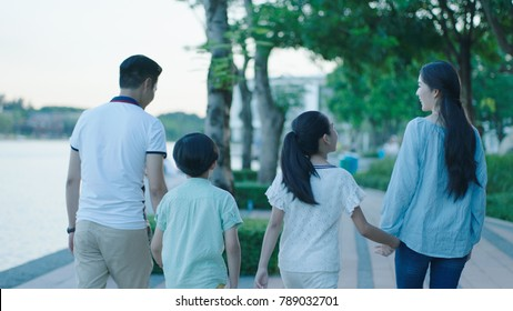 Rear view of Asian family smiling & walking on waterfront promenade at dusk