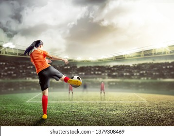 Rear view of asian football player woman in orange jersey kicking the ball on the football field at stadium
