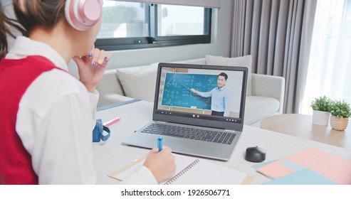 rear view of asian girl is learning math online through listening to male high school teacher teaching trigonometric function by  laptop at home and write down the note