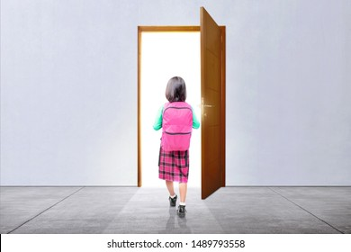Rear view of Asian little girl with a backpack walking through the door to going to school