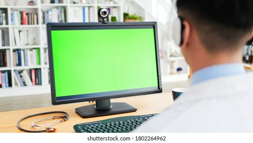 rear view of asian male doctor wear headphone and watch computer monitor with green screen