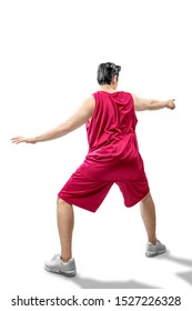 Rear view of Asian man basketball player in the pose of dribbling the ball isolated over white background