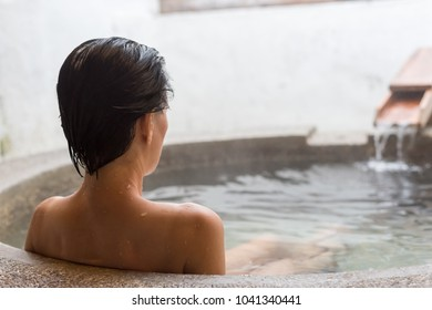 rear view of asian mature woman at the hot spring pool