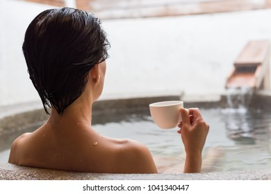 rear view of asian mature woman hold a cup of coffee at the hot spring pool