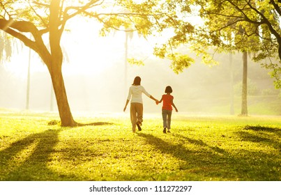 Rear view of Asian mother holding her daughter's hand running towards light