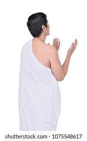 Rear view of asian muslim man in ihram cloth praying isolated over white background