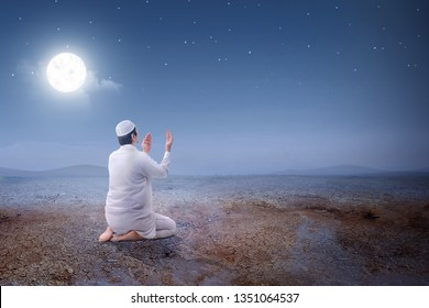 Rear view of asian muslim man sitting in pray position while raised hands and praying on the sand dune with moon and night scene background
