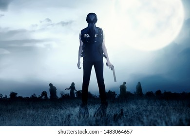 Rear view of Asian policewoman with the gun on her hand face the zombies on the grass field at night. Halloween concept