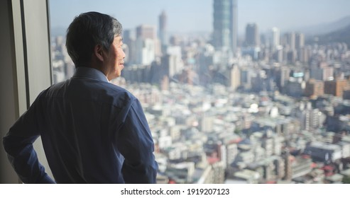 rear view of asian senior businessman is looking at city view near window in office