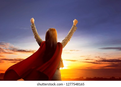 Rear view of asian super business woman with red cloak feel excited standing over sunset background