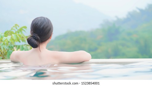 rear view of asian woman enjoy outdoor hot spring