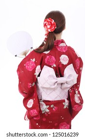 Rear view of asian woman in traditional clothes of kimono with paper fan